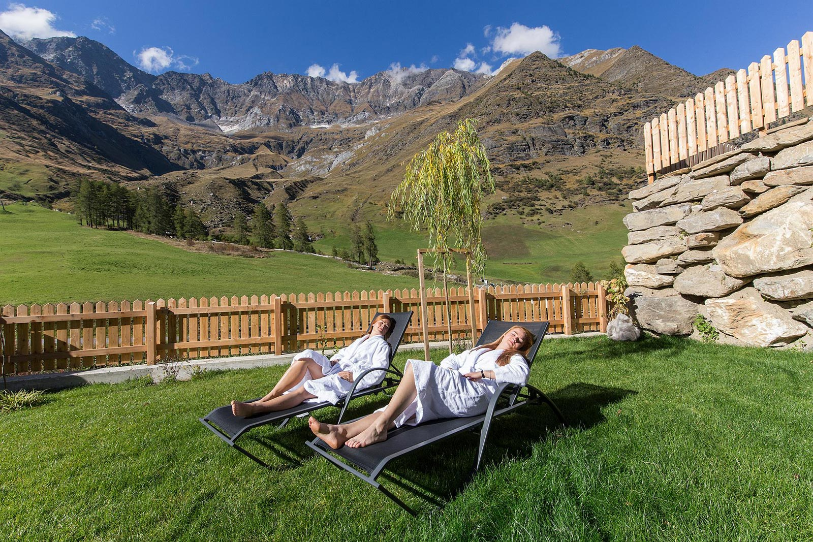 Two girls are relaxing in the garden of the Apartment in South Tyrol