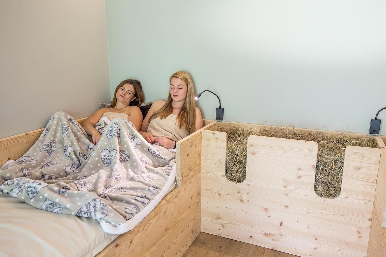 Two girls are relaxing on a hay bed at the Residence Marteshof